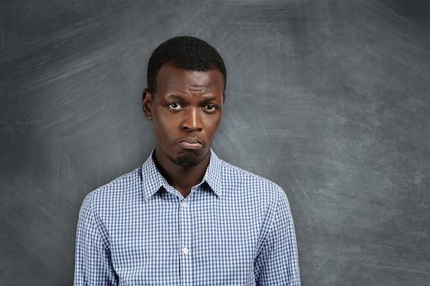 Estudante africano infeliz e triste com uma careta, descontente com sua reprovação nas provas. jovem professora negra insatisfeita e decepcionada com os resultados dos exames. Foto gratuita
