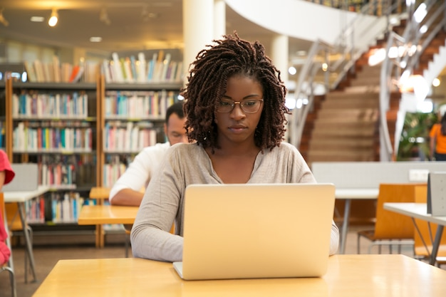 Estudante afro-americano sério trabalhando na pesquisa Foto gratuita