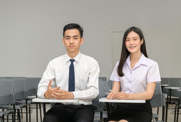 Estudante asiática com aparelho nos dentes e amigo em sala de aula Foto Premium
