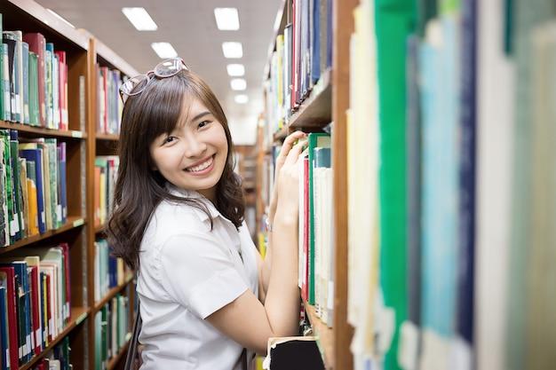 Estudante asiática na biblioteca Foto Premium