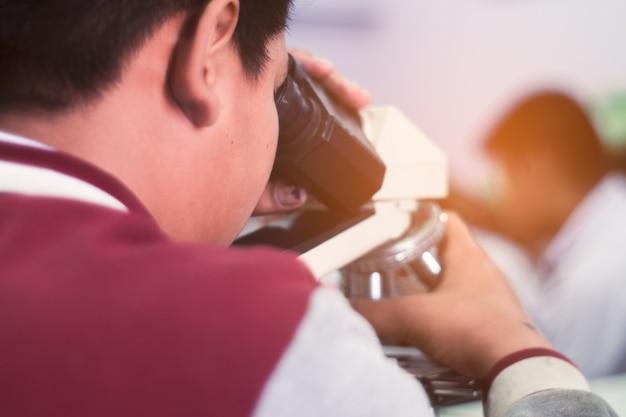 Estudante asiática que olha o microscópio na classe da ciência Foto Premium