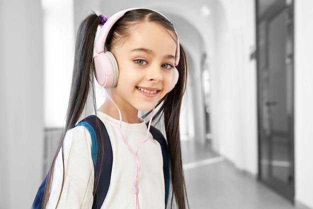 Estudante bonita, positiva que está no corredor da escola primária. Foto Premium
