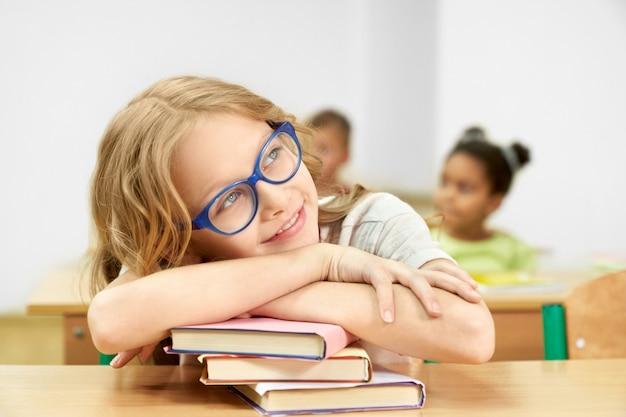 Estudante bonita que senta-se na mesa na sala de aula, cabeça de inclinação na pilha de livros. Foto Premium