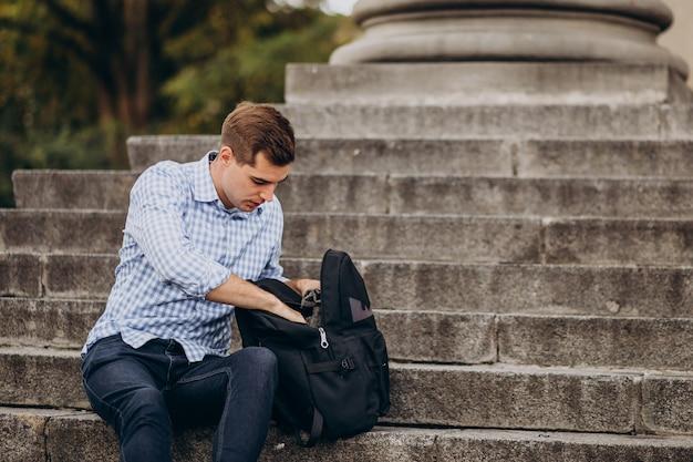Estudante bonito sentado na escada da universidade estudando Foto gratuita