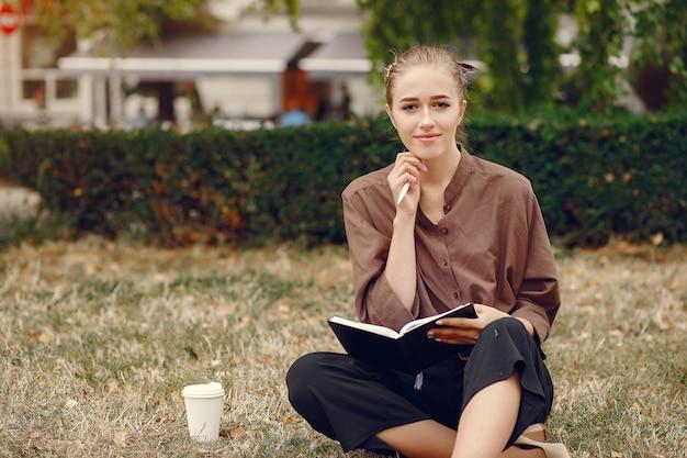 Estudante bonito, trabalhando em um parque e usar o notebook Foto gratuita