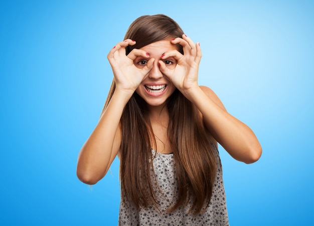 Estudante brincalhão com o gesto dos vidros sobre o fundo azul Foto gratuita