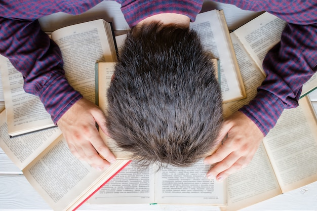 Estudante cansado adormeceu nos livros Foto Premium