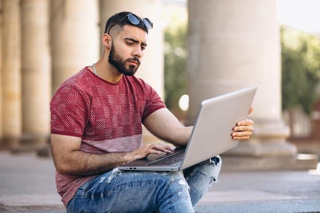 Estudante com laptop pela universidade Foto gratuita