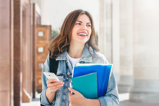 Estudante da moça que sorri contra a universidade. linda garota estudante detém pastas, cadernos e celular nas mãos. aprendizagem, educação Foto Premium