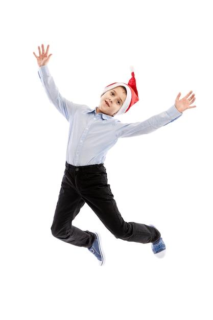 Estudante de salto sorridente no chapéu de papai noel. altura toda. espírito de natal. isolado sobre o fundo branco vertical. Foto Premium