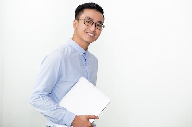 Estudante de sorriso nos vidros laptop transportando Foto gratuita