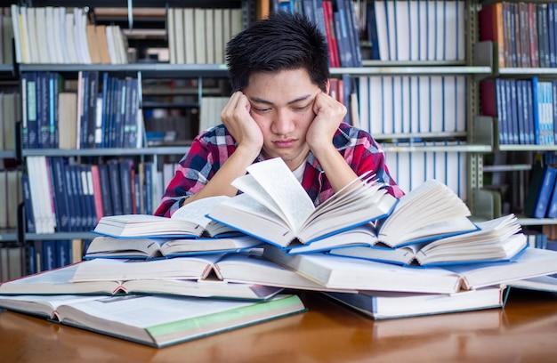 Estudante do sexo masculino asiático está cansado e estressado na biblioteca Foto Premium