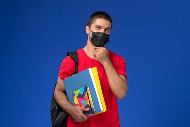 Estudante do sexo masculino de vista frontal em t-shirt vermelha, usando mochila em máscara estéril preta segurando cadernos pensando sobre o fundo azul. Foto gratuita