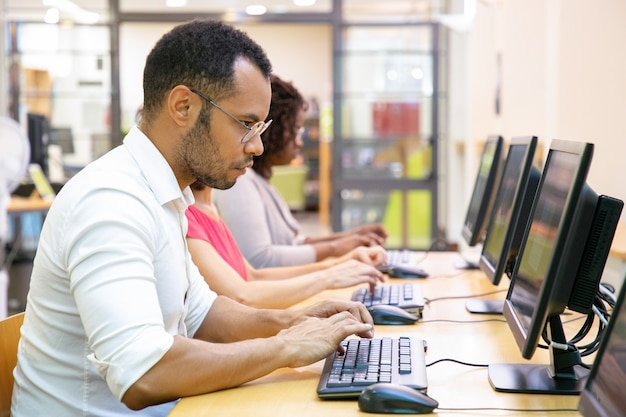 Estudante do sexo masculino extremamente focado fazendo teste on-line Foto gratuita