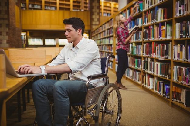 Estudante, em, cadeira rodas, digitando, ligado, seu, laptop, enquanto, mulher, busca livros, em, biblioteca Foto Premium