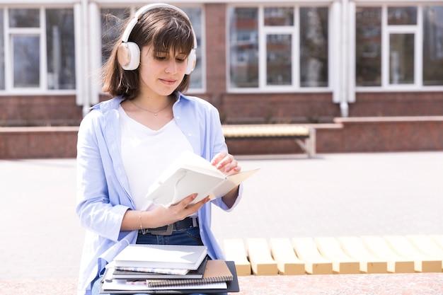 Estudante em fones de ouvido, lendo notas Foto gratuita