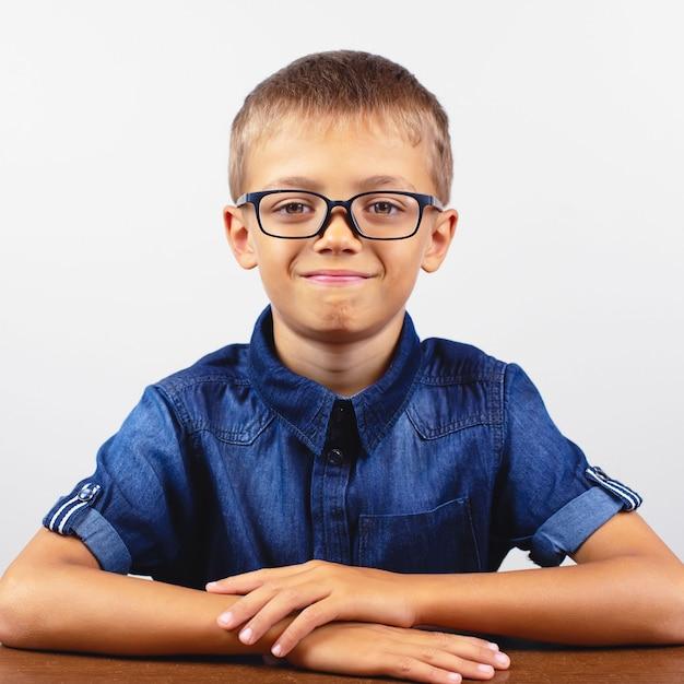 Estudante em uma camisa azul, sentado à mesa. menino, com, óculos Foto Premium
