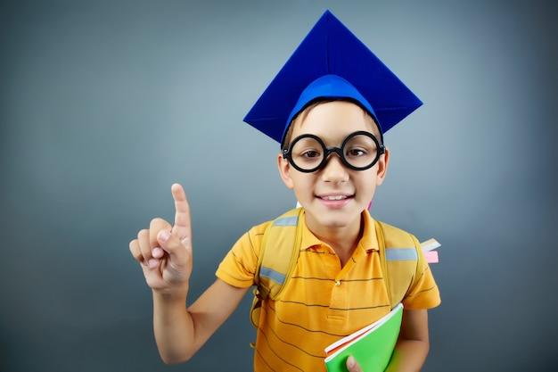 Estudante encantador com tampão azul da graduação Foto gratuita