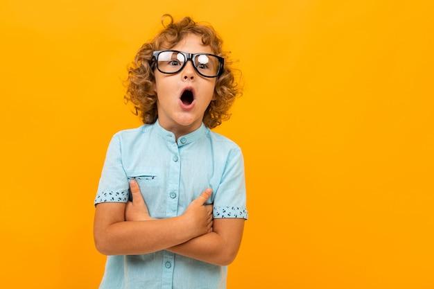 Estudante encaracolado chocado com óculos em um amarelo Foto Premium