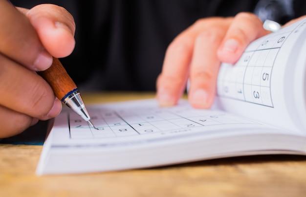 Estudante está tentando resolver sudoku com lápis de cor Foto Premium