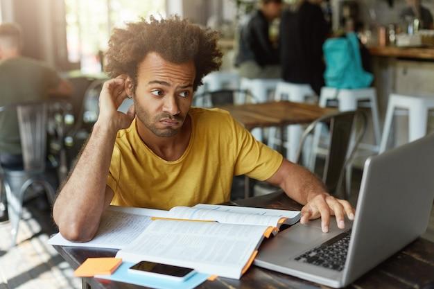 Estudante estiloso com penteado africano com olhar duvidoso enquanto olha para o laptop sem entender o novo material tentando encontrar uma boa explicação na internet Foto gratuita