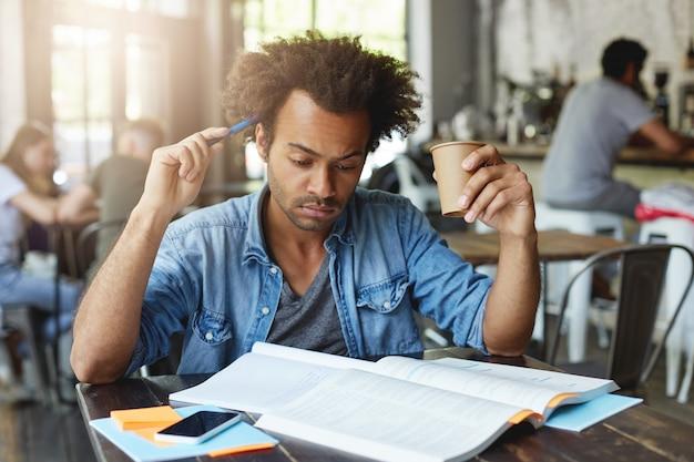 Estudante europeu negro, concentrado e pensativo com penteado afro, coçando a cabeça com caneta, bebendo chá quente em um café, preparando-se para uma aula de francês na faculdade, traduzindo artigo em livro didático Foto gratuita