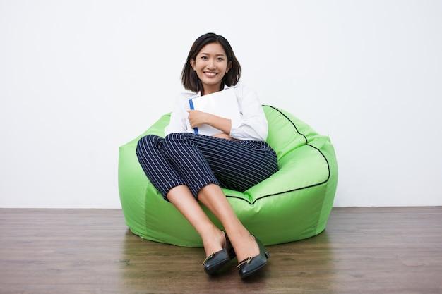 Estudante fêmea asiático feliz que descansa em beanbag Foto gratuita