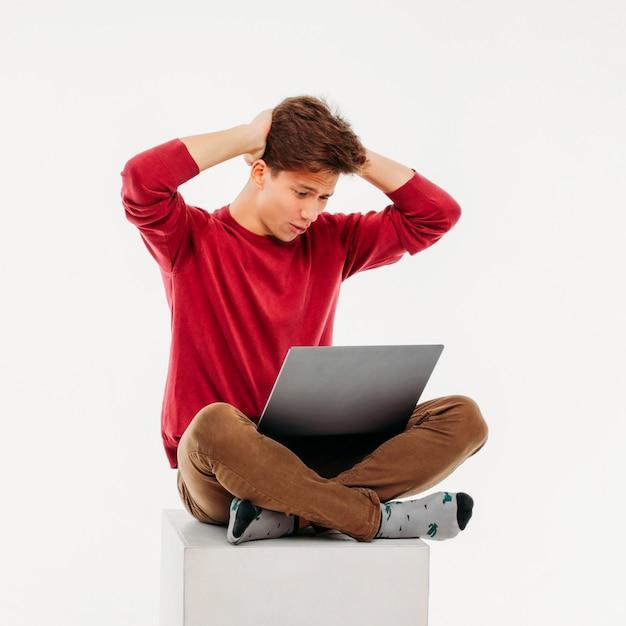 Estudante frustrante jovem no laptop em fundo branco Foto Premium