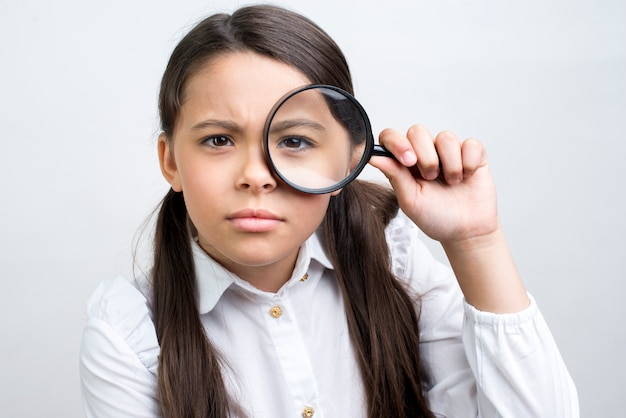Estudante hispânica atenta, olhando através de lupa Foto gratuita