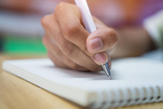 Estudante homem, levando, escrita, notas, ligado, caderno, com, caneta, em, biblioteca, em, faculdade, universidade Foto Premium