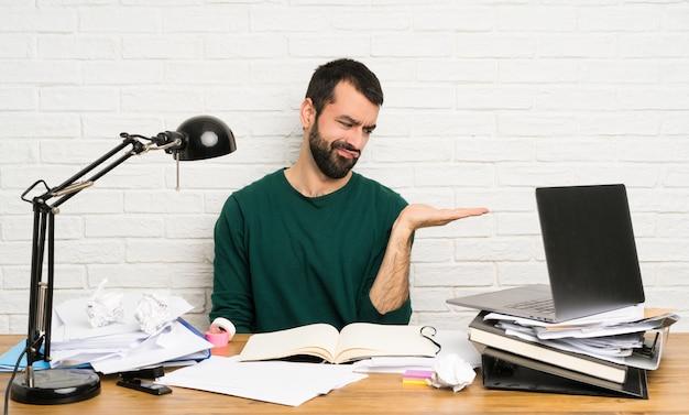 Estudante homem segurando copyspace com dúvidas Foto Premium