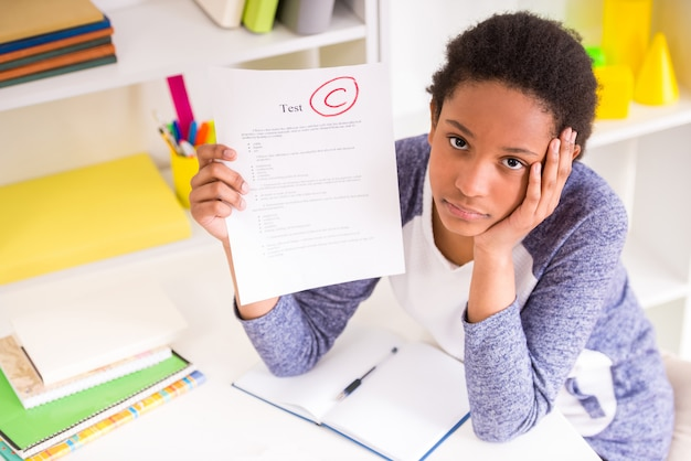 Estudante infeliz mulata sentado à mesa. Foto Premium