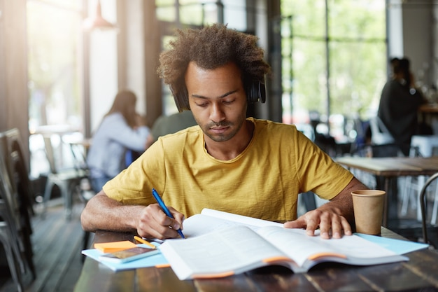 Estudante inteligente de pele escura escrevendo algo de um livro e ouvindo um audiolivro em seus fones de ouvido enquanto está sentado no refeitório durante seu intervalo, bebendo café para viagem e trabalhando duro Foto gratuita