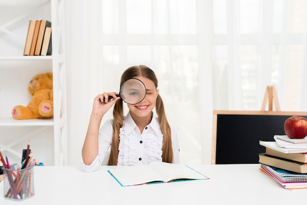 Estudante inteligente, olhando através de lupa Foto gratuita