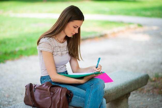 Estudante jovem estudando ao ar livre na frente de sua escola Foto Premium