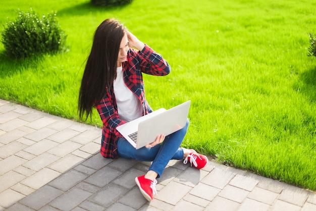 Estudante jovem morena trabalhando ao ar livre Foto Premium
