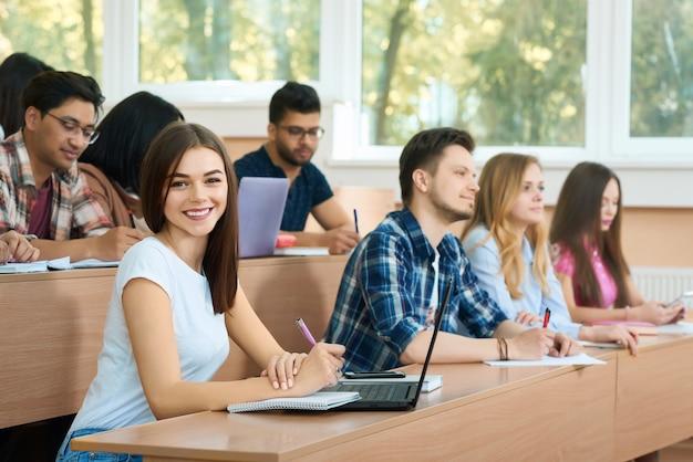 Estudante novo que olha a câmera que senta-se na universidade. Foto Premium