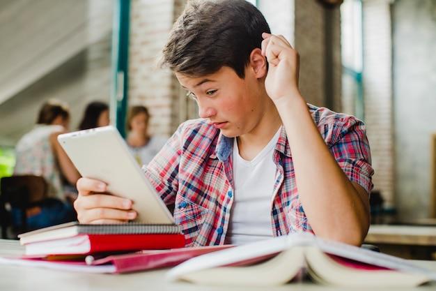 Estudante olhando com perplexidade no comprimido Foto gratuita