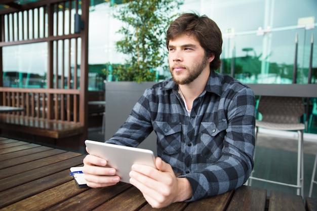 Estudante pensativo usando tablet Foto gratuita