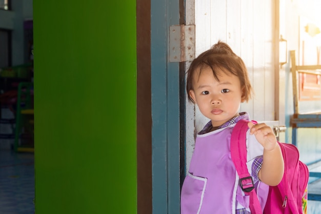 Estudante pré-escolar asiático da menina em geral uniforme e saco vermelho que vai à escola, de volta à escola. Foto Premium