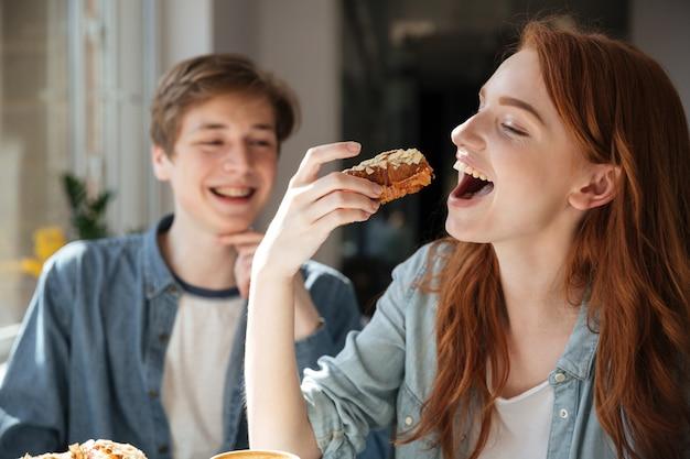 Estudante ruiva comendo sobremesa Foto gratuita