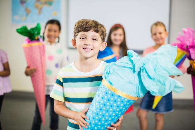 Estudante segurando o presente na sala de aula Foto Premium