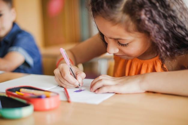 Estudante sentada no desenho da mesa Foto gratuita