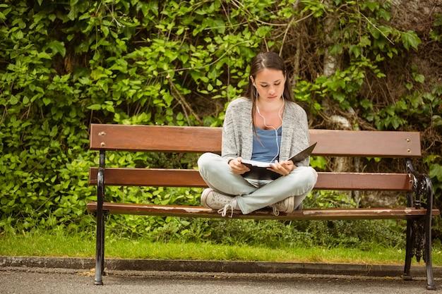 Estudante, sentar-se banco, escutar música, com, telefone móvel, e, revisar, em, parque, em, escola Foto Premium