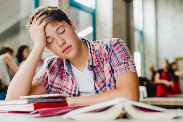 Estudante sonolento na mesa Foto gratuita