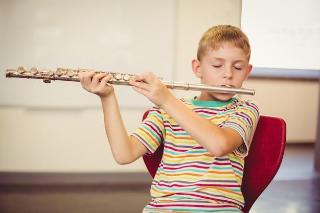 Estudante tocando flauta na sala de aula Foto Premium