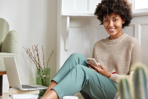 Estudante universitária de pele escura, muito sorridente, com aparência despreocupada, vestida com roupas casuais e sentada no chão Foto gratuita