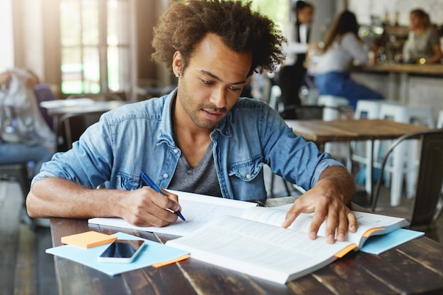 Estudante universitário afro-americano elegante e bonito estudando em um café Foto gratuita