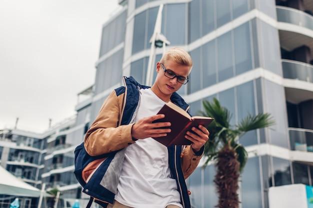 Estudante universitário, com, mochila, livro leitura, andar, por, modernos, hotel, ligado, praia tropical Foto Premium