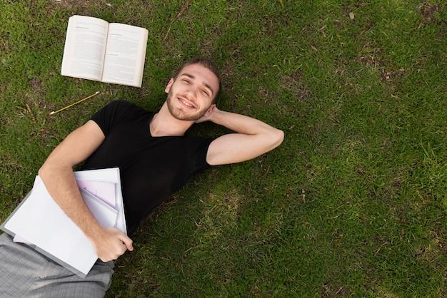 Estudante universitário, dando um tempo na grama Foto gratuita
